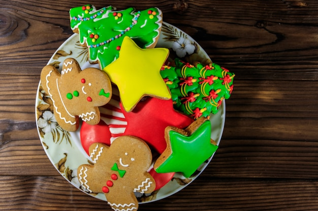 Prato com saborosos biscoitos de gengibre festivos de natal em forma de árvore de natal, homem-biscoito, estrela e meia de natal na mesa de madeira. vista do topo