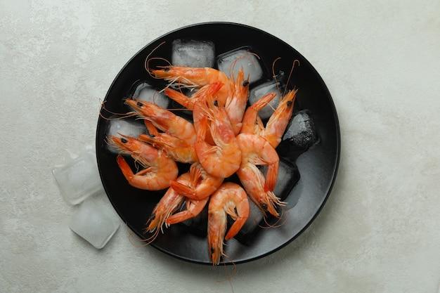 Prato com saborosos camarões e cubos de gelo na mesa texturizada branca
