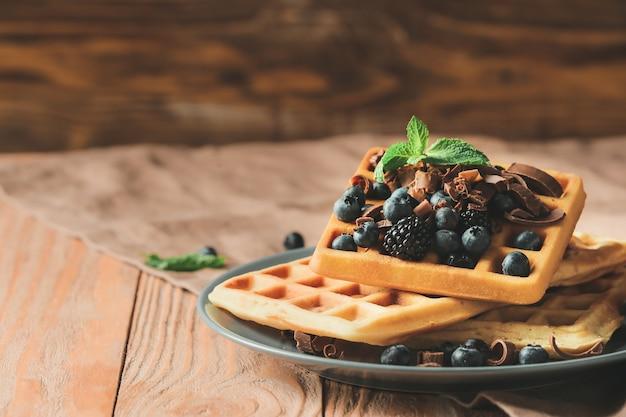 Prato com saborosos waffles e frutas vermelhas na mesa