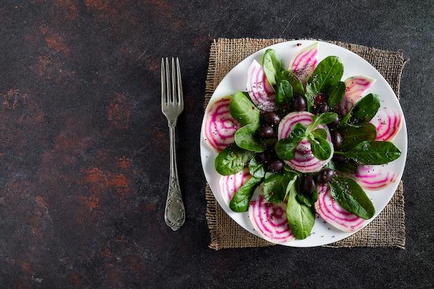 Prato com salada de beterraba, da raiz às folhas, com salada de milho e azeitonas pretas