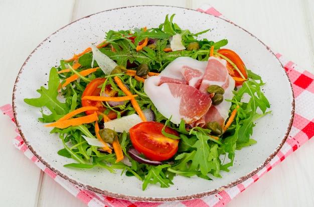 Prato com salada fresca de folhas, fatias de parmesão e presunto
