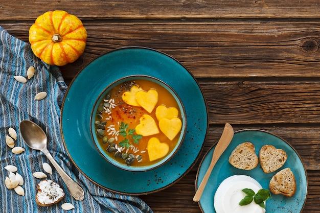 Prato com sopa de creme de abóbora caseiro fresco com sementes e torradas de forma de coração