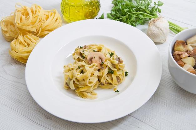 Prato com tagliatelle e cogumelos e ingredientes frescos