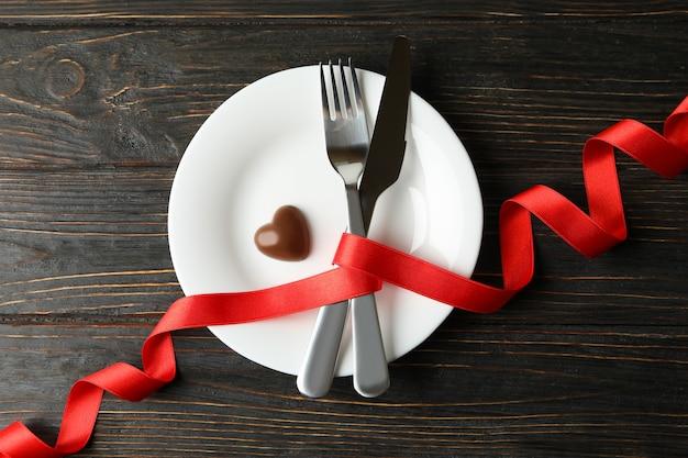 Prato com talheres, fita e coração de chocolate em fundo de madeira
