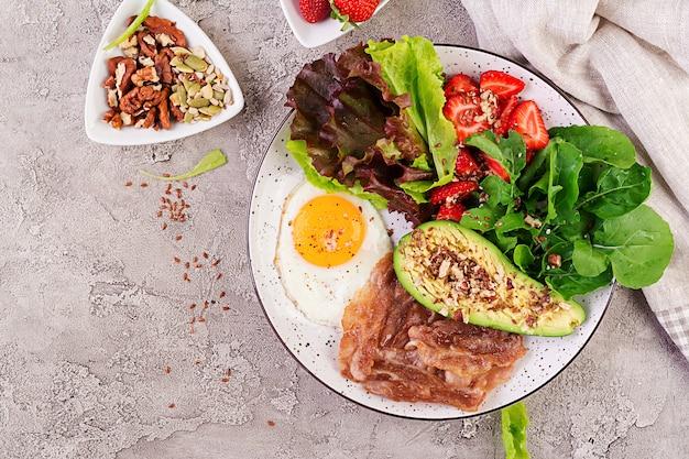 Prato com um alimento de dieta ceto, ovo frito, bacon, abacate, rúcula e morangos, café da manhã keto, vista superior