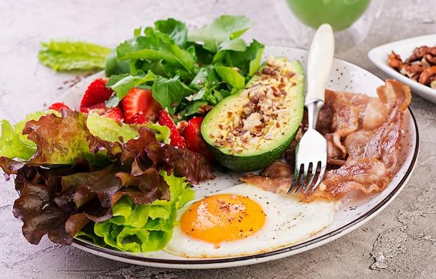 Prato com um alimento de dieta ceto, ovo frito, bacon, abacate, rúcula e morangos, café da manhã keto.