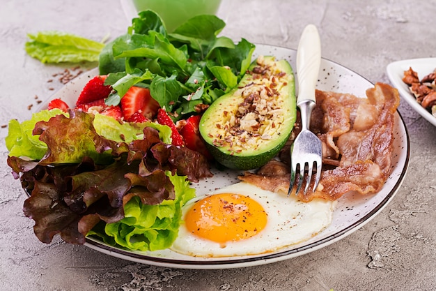 Prato com um alimento de dieta ceto. ovo frito, bacon, abacate, rúcula e morangos. keto café da manhã.