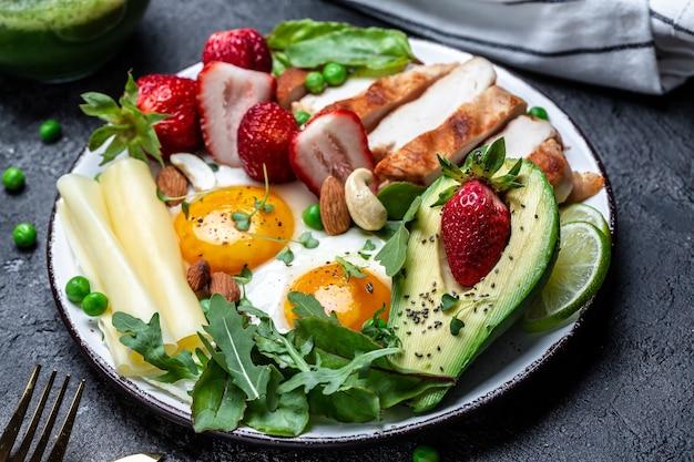 Prato com um alimento dietético cetônico. ovo frito, abacate, morango, filé de frango grelhado, queijo, nozes e rúcula. café da manhã keto. fundo de receita de comida. fechar-se,