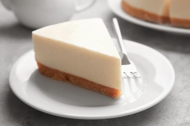 Prato com um pedaço de delicioso cheesecake na mesa