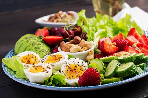 Prato com uma comida de dieta paleo, ovos cozidos, abacate, pepino, nozes, cereja e morangos, café da manhã paleo.