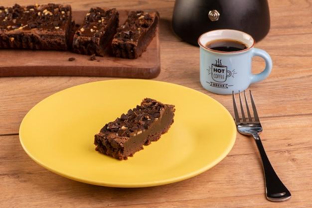 Prato com uma fatia de brownie, uma cafeteira e uma xícara de café.
