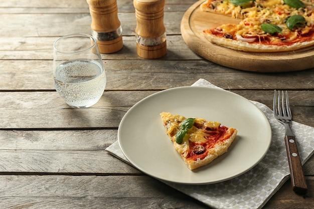Prato com uma fatia de pizza saborosa na mesa de madeira