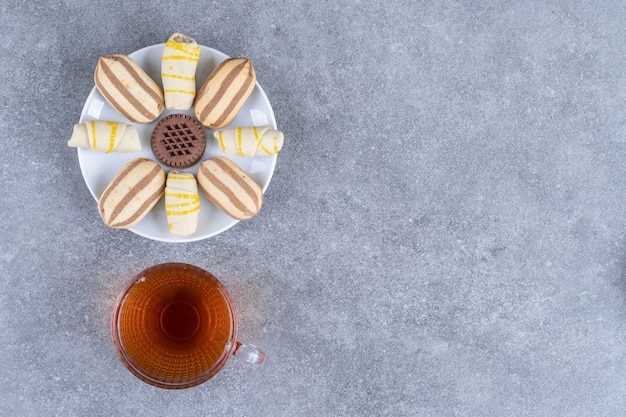 Prato com vários biscoitos e copo de chá na superfície de mármore