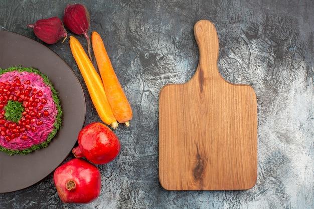 Prato com vista de cima em close-up um prato apetitoso romãs legumes a tábua de cortar