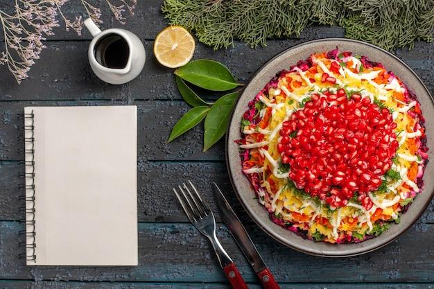 Prato com vista de close-up superior com prato de romãs com romãs ao lado da faca de caderno branco limão e ramos de abeto garfo na mesa escura