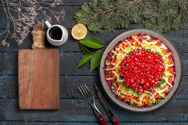 Prato com vista de close-up superior com prato de romãs com romãs ao lado da faca de tábua de corte de óleo de limão e ramos de abeto garfo na mesa escura