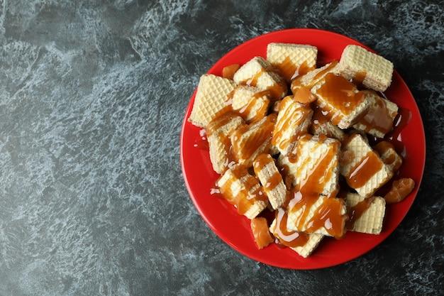 Prato com wafers com caramelo na mesa preta esfumada