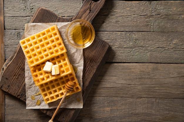 Prato com waffle delicioso mel e uma fatia de manteiga. sobre um fundo de madeira. vista de cima