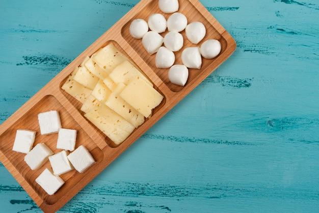 Prato compartimentado de queijos com diferentes queijos, em mesa rústica de madeira