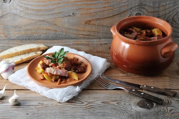 Prato cozido em uma panela com batatas, feijão, defumado em uma panela de barro