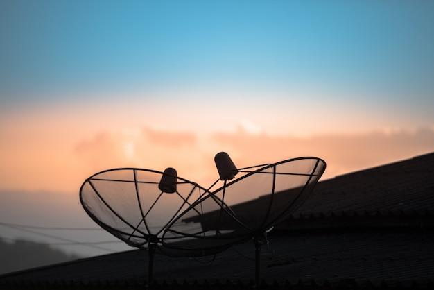 Prato da antena parabólica ou da antena no telhado da casa com o céu azul bonito na manhã.