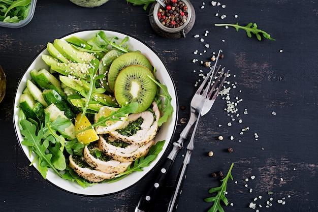 Prato da bacia de buddha com faixa da galinha, abacate, pepino, salada fresca da rúcula e sésamo.