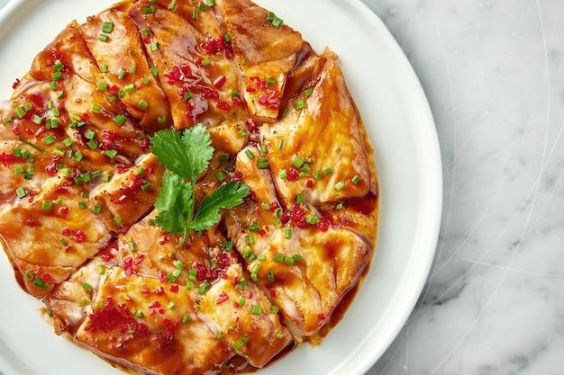 Prato da culinária mexicana - tostada com salmão, molho agridoce, cebola, coentro, servido em prato branco sobre mesa de mármore. close up, foco seletivo
