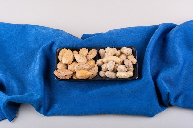 Prato de amendoins com casca crua e amendoim em pano azul. foto de alta qualidade