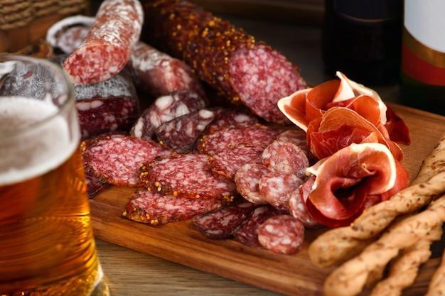 Prato de antepastos com bacon, carne seca, salame, grissini crocante com queijo. um aperitivo de carne é uma ótima ideia para uma cerveja.