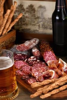 Prato de antepastos com bacon, carne seca, salame, grissini crocante com queijo.