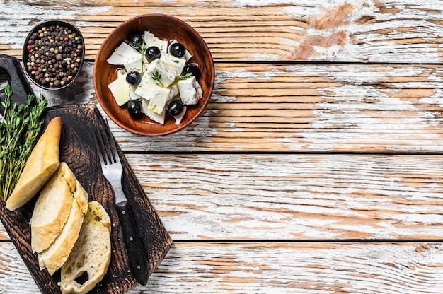 Prato de antepastos com queijo feta fresco, pão e azeitonas.