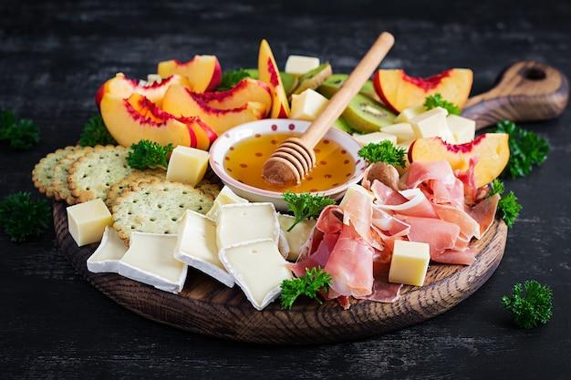 Prato de antipasto italiano com presunto, queijo e frutas em um fundo escuro.