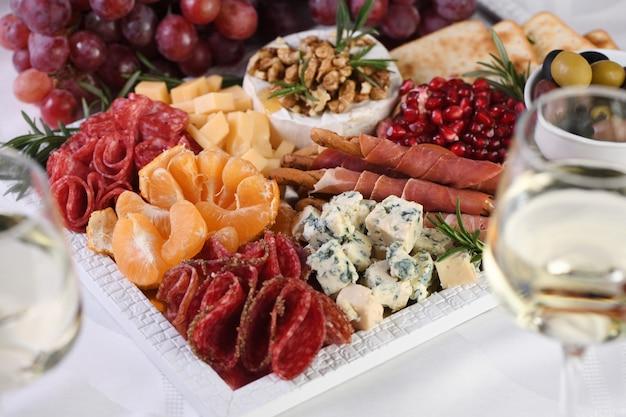 Prato de aperitivos variados de iguarias de salame e queijo, grissini envolto em presunto de parma, azeitonas e citrinos. um antipasto original para uma festa.