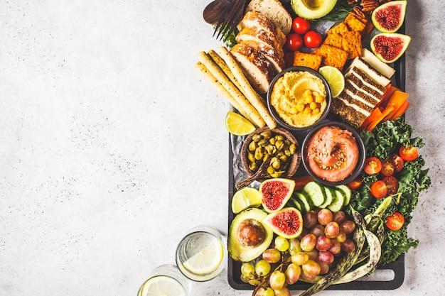 Prato de aperitivos veganos, hummus, tofu, legumes, frutas e pão