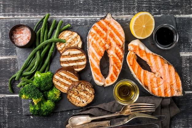 Prato de ardósia com bifes de salmão grelhados e vegetais na mesa de madeira preta, vista superior
