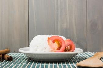 Prato de arroz com fatia de tomate; paus de canela e espátula de madeira em placemat