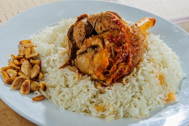 Prato de arroz com perna de carneiro assada.