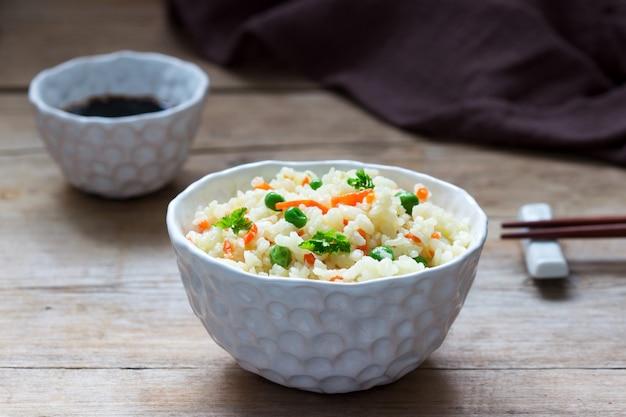 Prato de arroz vegetariano com legumes e ervilhas verdes em um fundo de madeira.