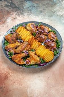 Prato de asas de frango com apetitosas batatas asas de frango cebola ervas