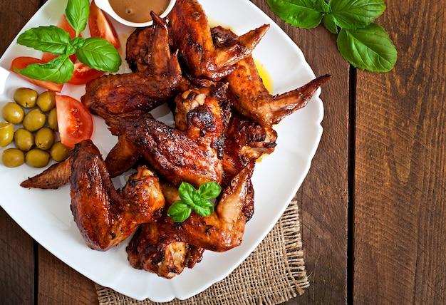 Prato de asas de frango na mesa de madeira