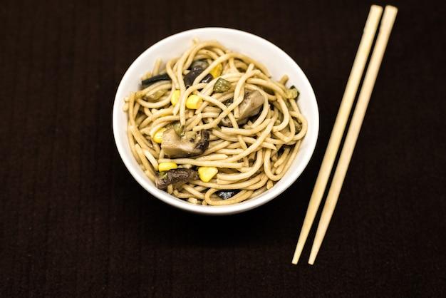 Prato, de, asiático, noddles, em, um, redondo branco, tigela, com, chopsticks