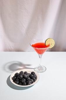 Prato de bagas azuis com bebida cocktail acima da mesa branca