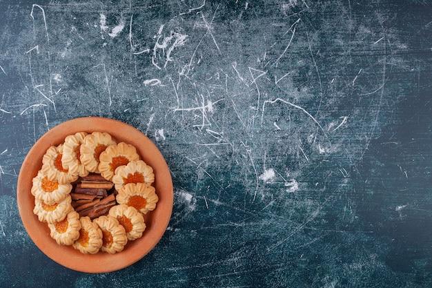 Prato de barro cheio de biscoitos de geléia e paus de canela no mármore.