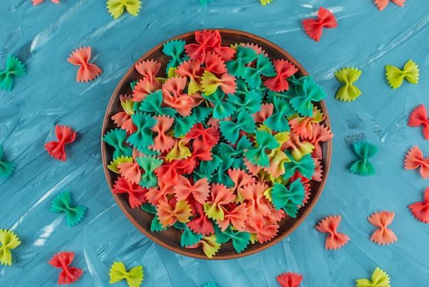 Prato de barro com macarrão farfalle cru colorido na superfície azul