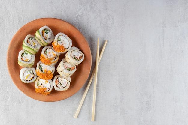 Prato de barro com vários rolos de sushi colocado sobre uma superfície de pedra