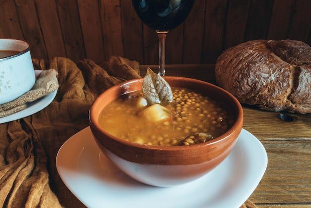 Prato de barro de lentilhas com batatas e um copo de vinho no fundo de madeira