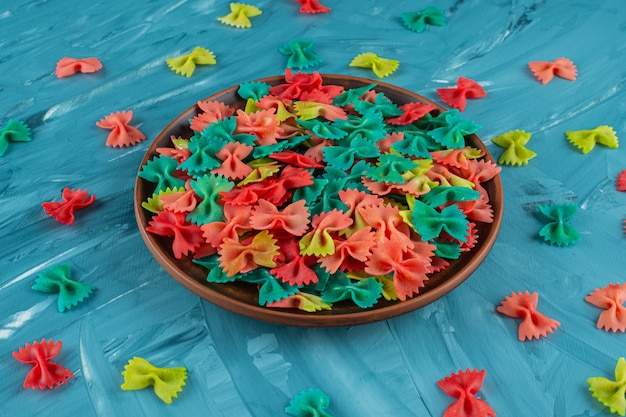 Prato de barro de macarrão farfalle cru colorido sobre fundo azul.