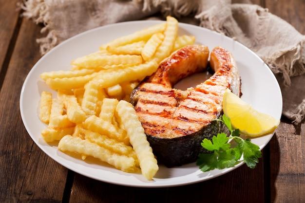 Prato de bife de salmão grelhado com batatas fritas na mesa de madeira