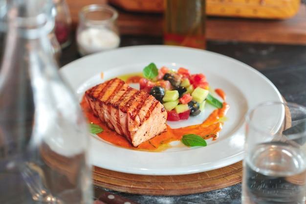 Prato de bife de salmão grelhado com legumes na mesa de madeira
