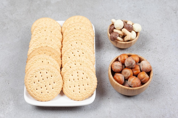 Prato de biscoitos ao lado de tigelas de cogumelos de avelã e chocolate no fundo de mármore. foto de alta qualidade